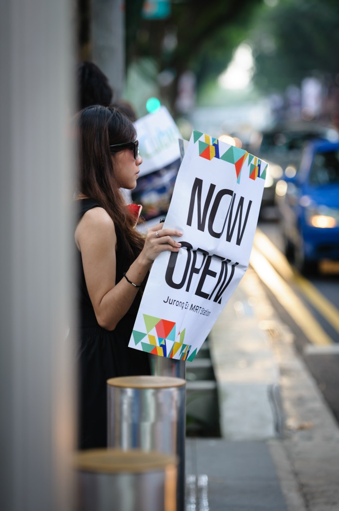 """Street photography - Girl holding newspaper that says """"Now Open"""""""