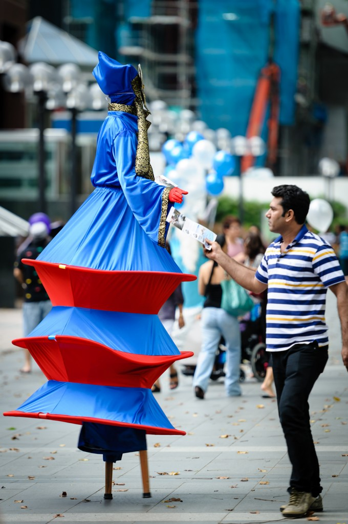 Street photography - man taking a flyer from a person on stilts