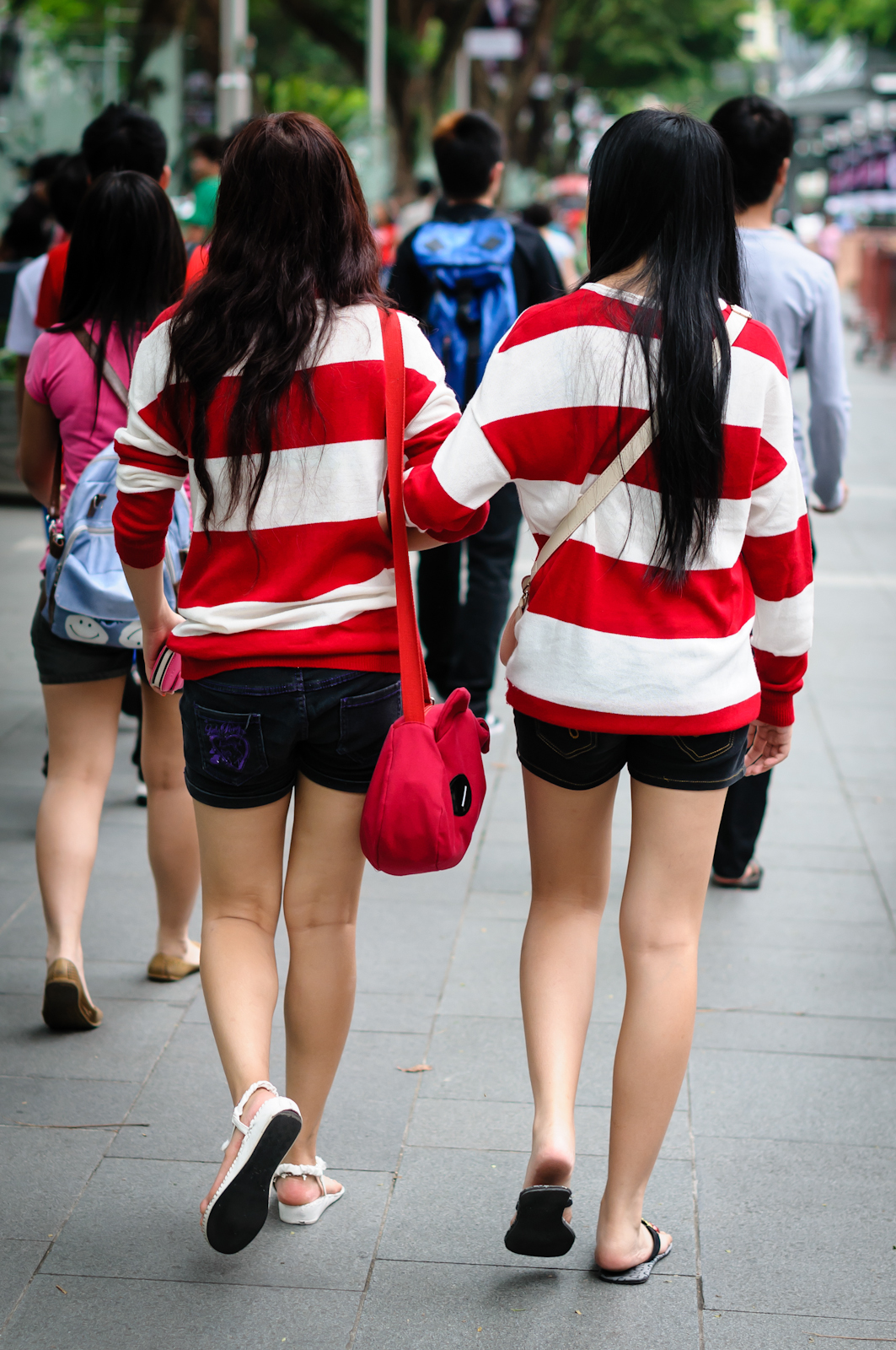 Street photography - two girls in red and white stripes holding hands