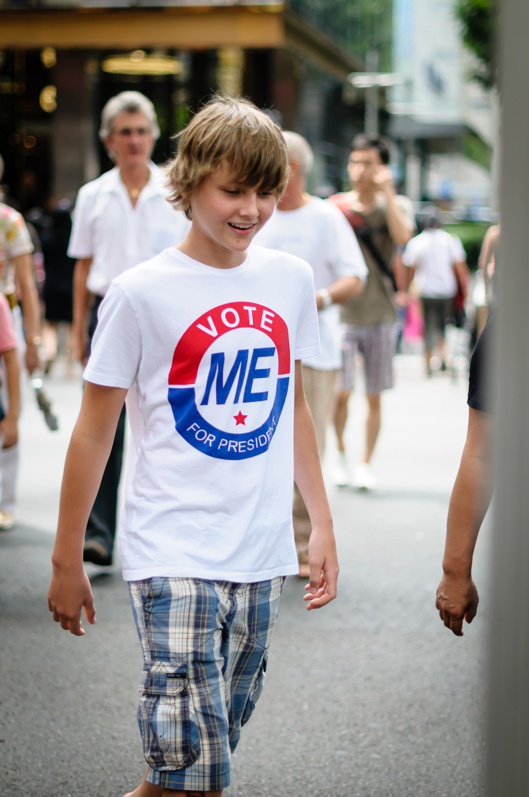 Street photography - boy wearing t-shirt that says vote me for president