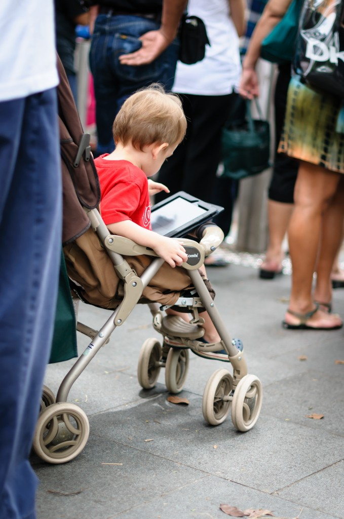 Street photography - child in pram playing with iPad