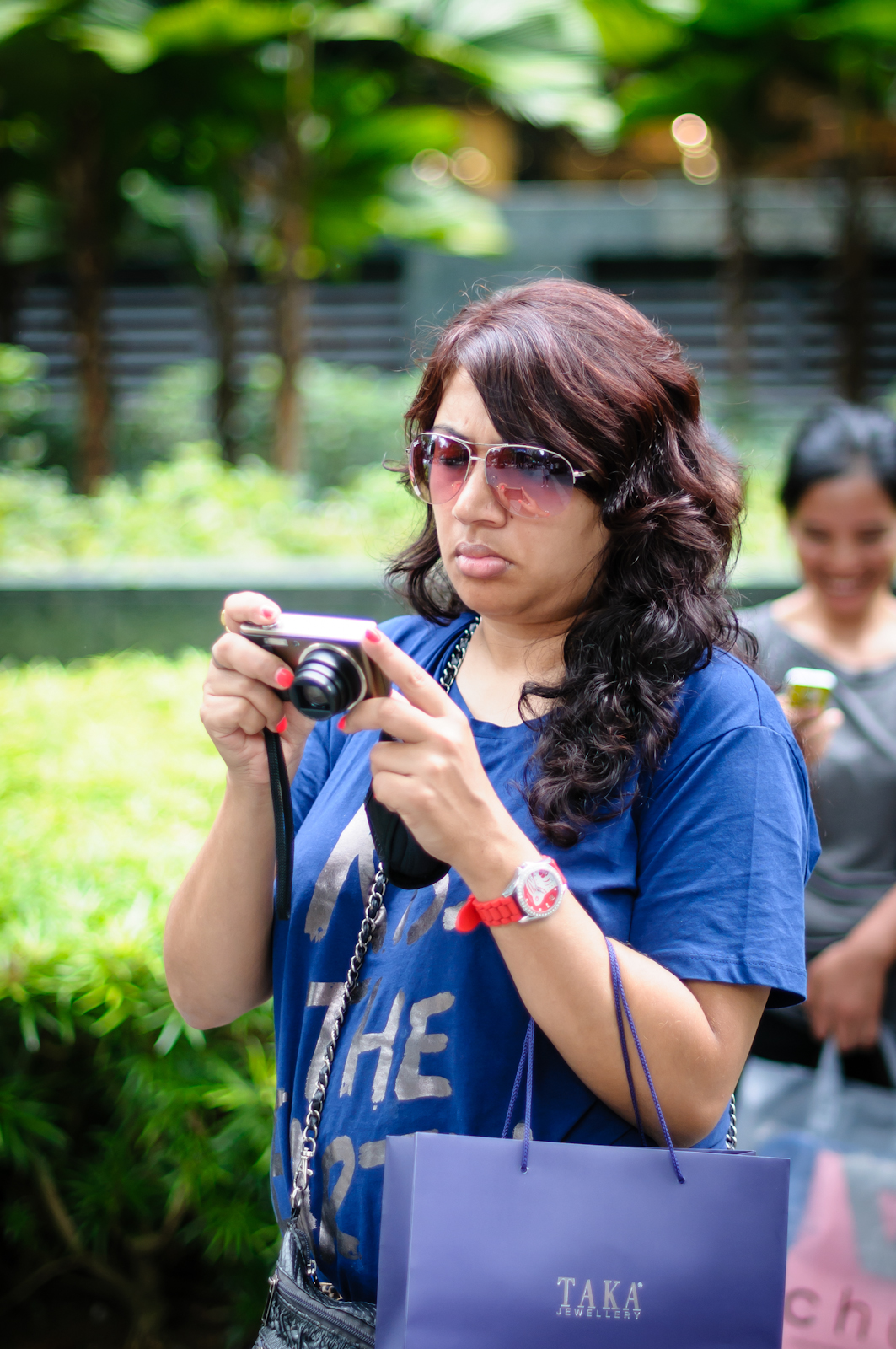 Street photography - tourist looking at her camera