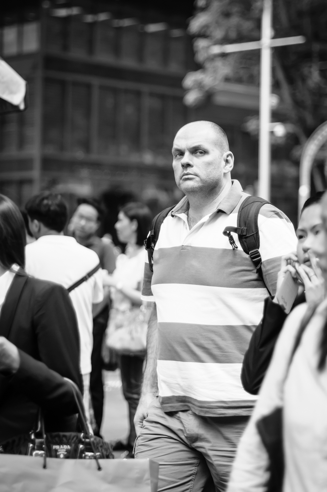 Street photography - man in broad-striped polo t-shirt looking at the camera