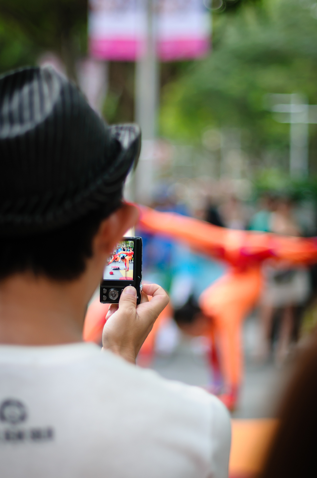 Street photography - Man taking a photo of a street performer