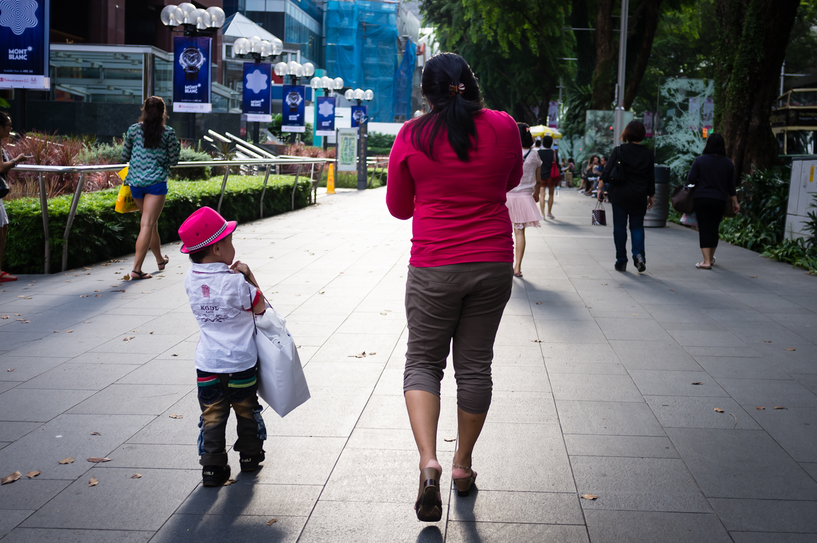 Street photography - Boy carrying shopping bag for his mother