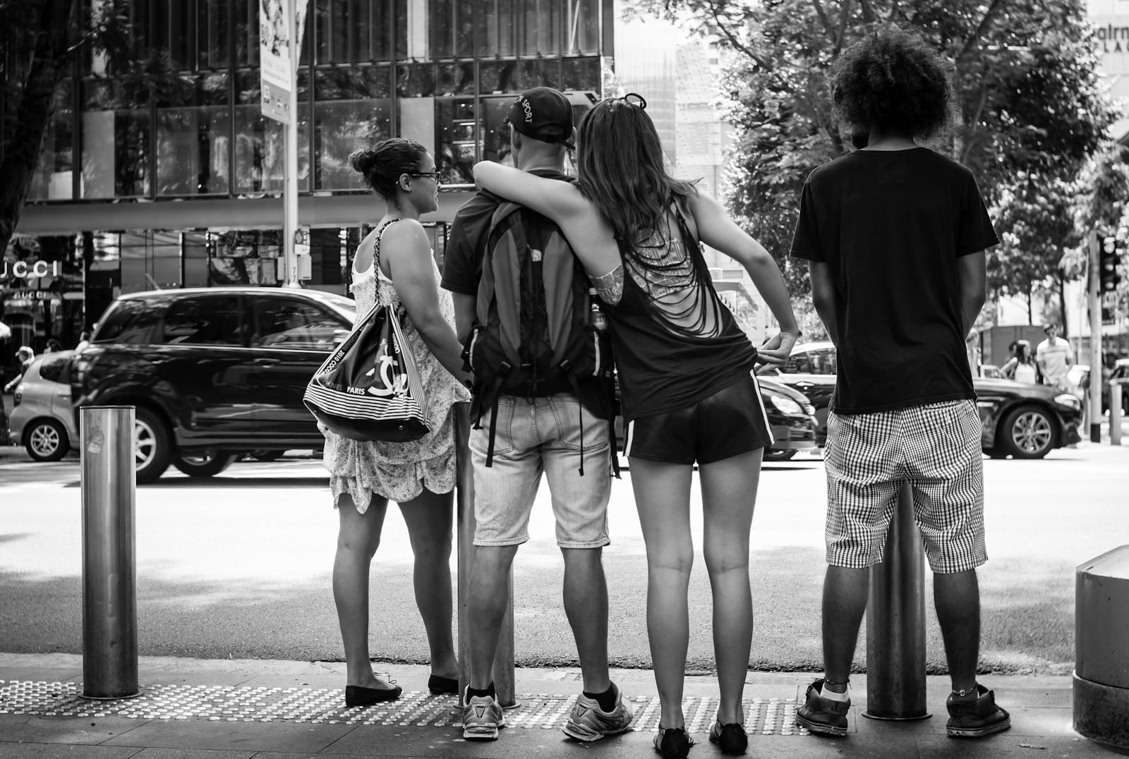 Street photography - four friends waiting to cross the road