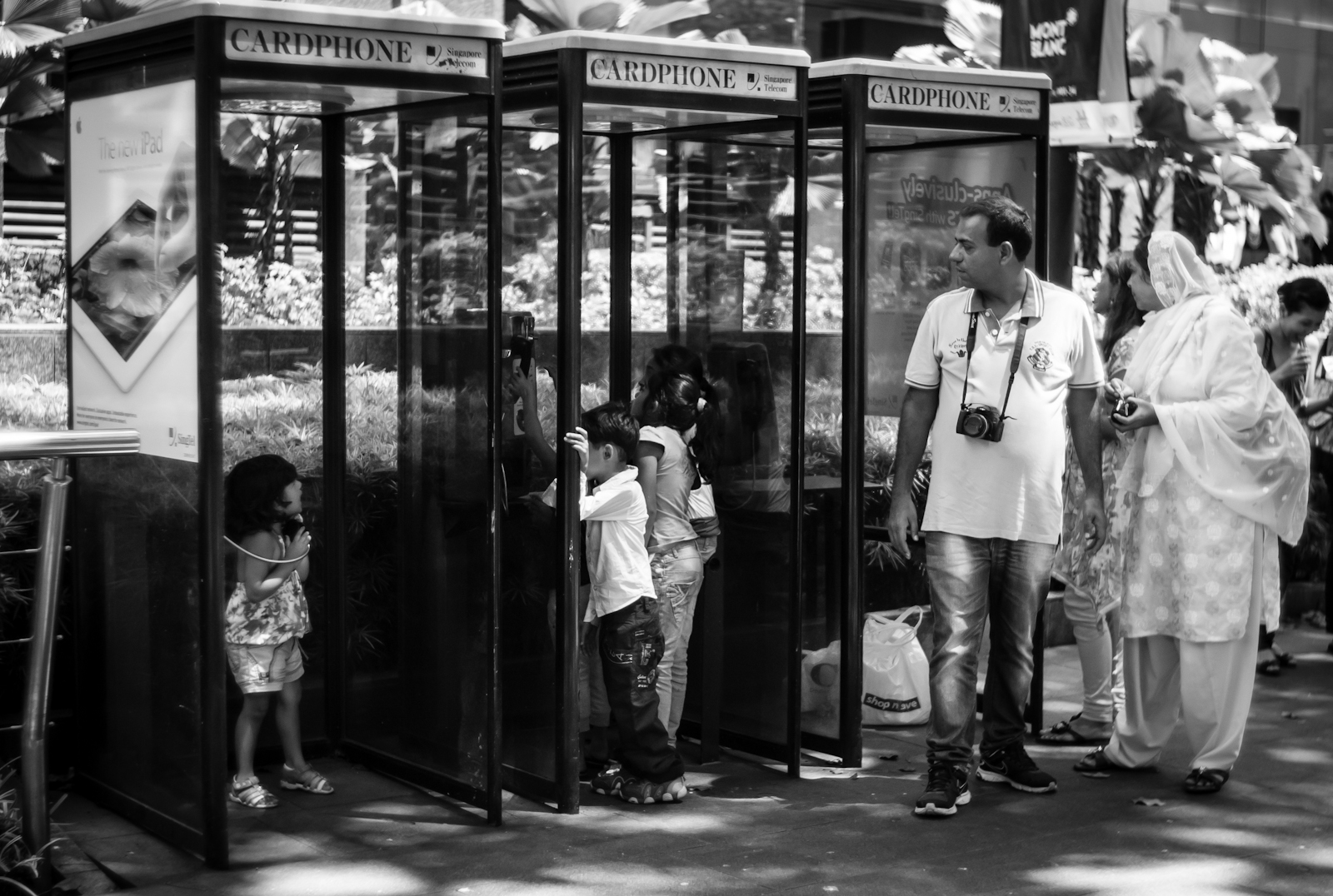 Street photography - tourist family playing with a phone booth in Orchard Road