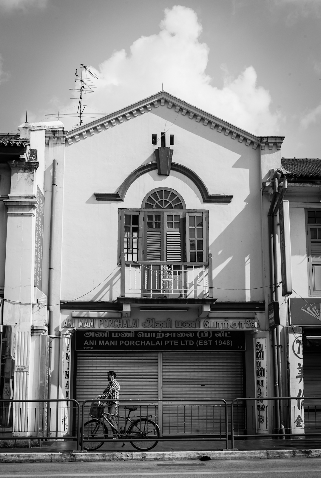 Street photography - Man pushing his bicycle past a shop house in Little India