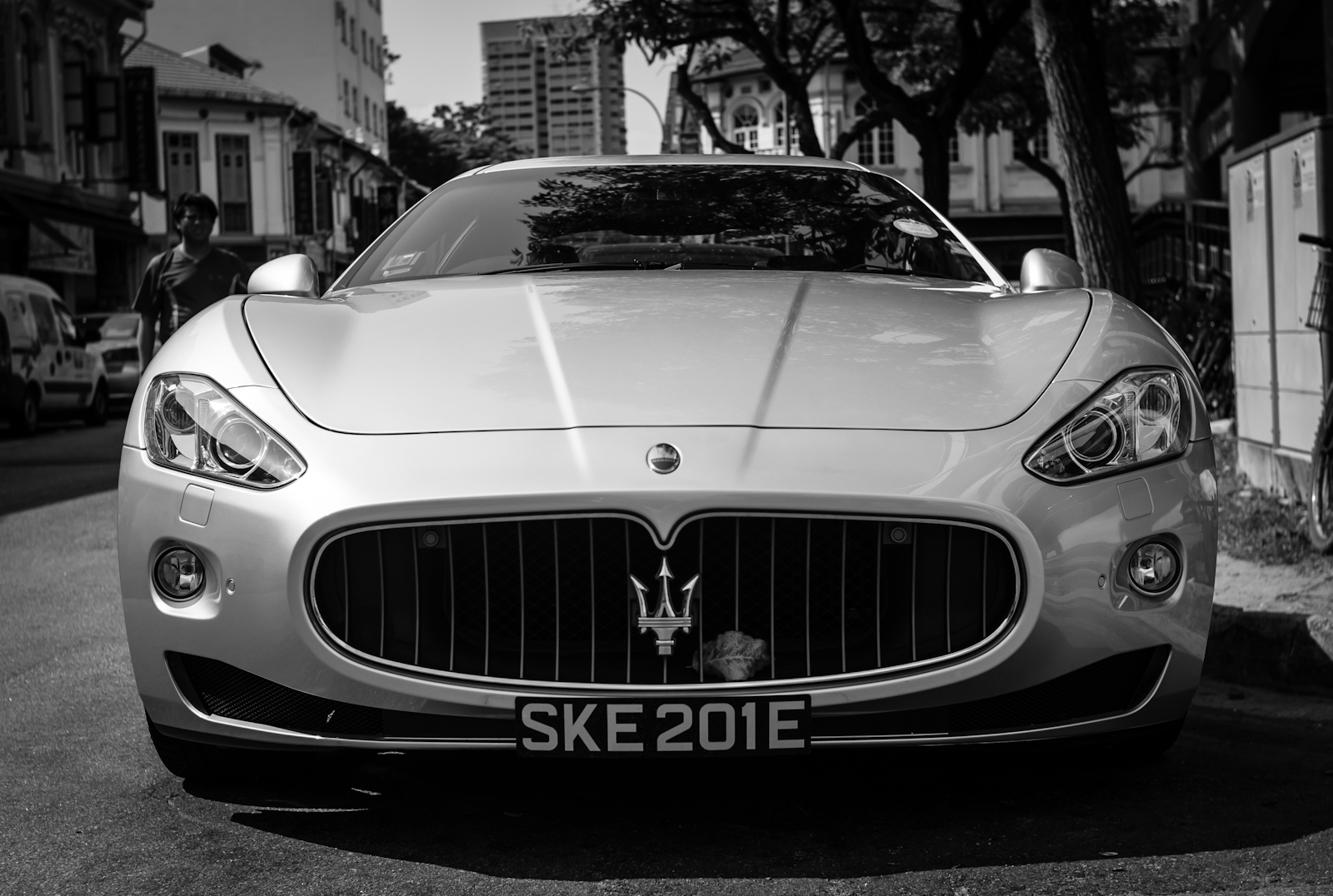Street photography - a dried leaf stuck on the front of a Maserati