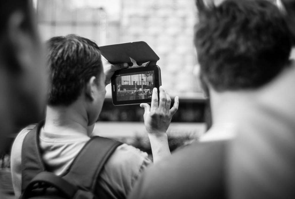 Street photography - Man recording a video with his tablet