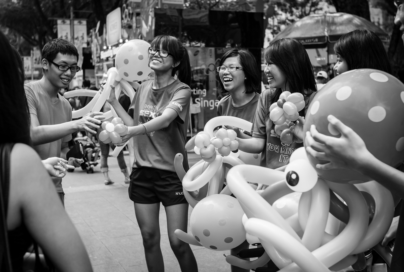 Boy buying a balloon sculpture from student volunteers
