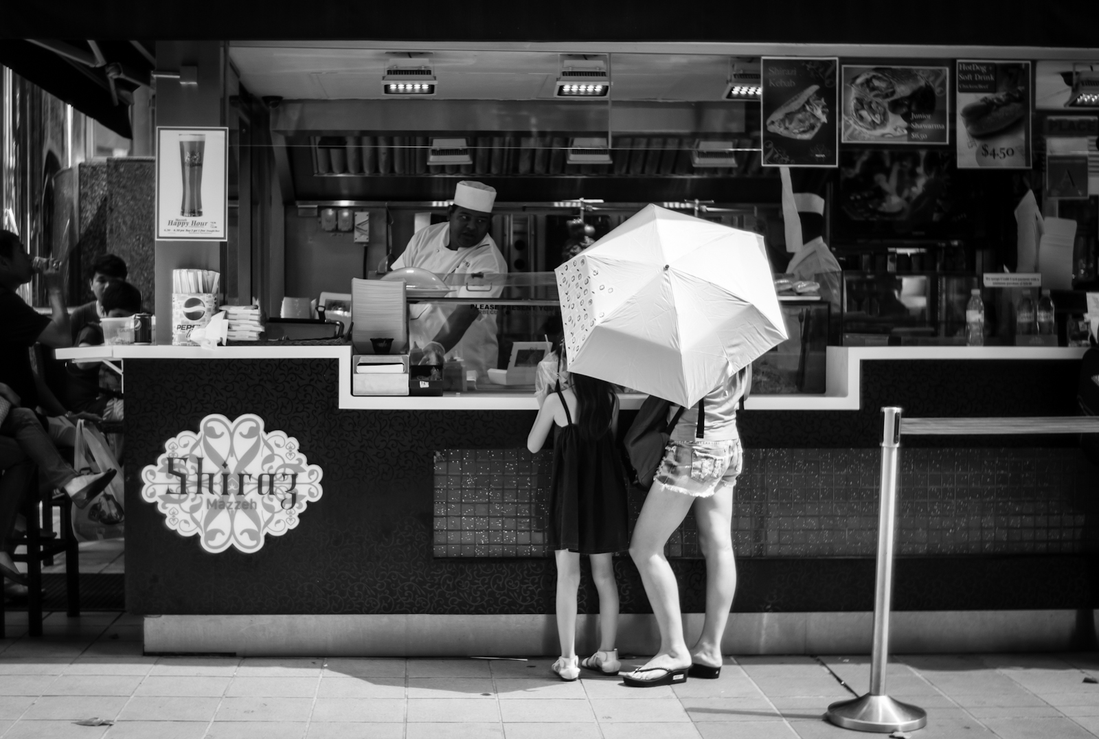 Mother and daughter standing beneath their umbrella while ordering food