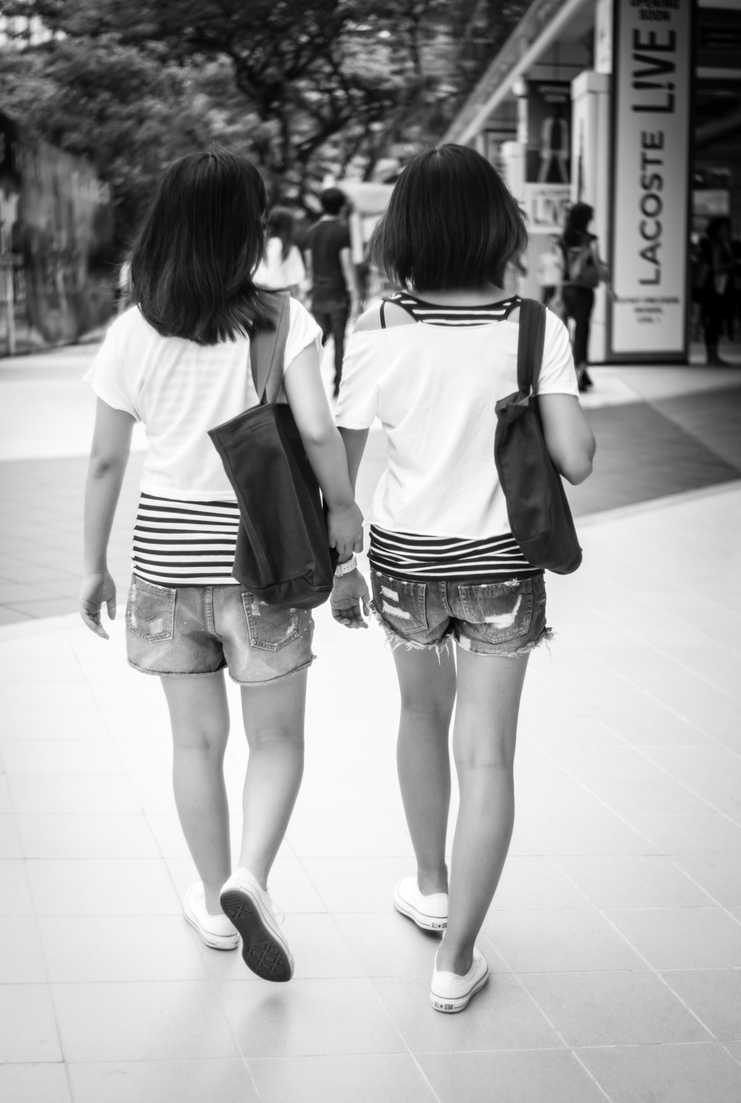 Two girls in almost identical clothing, shoes and bags