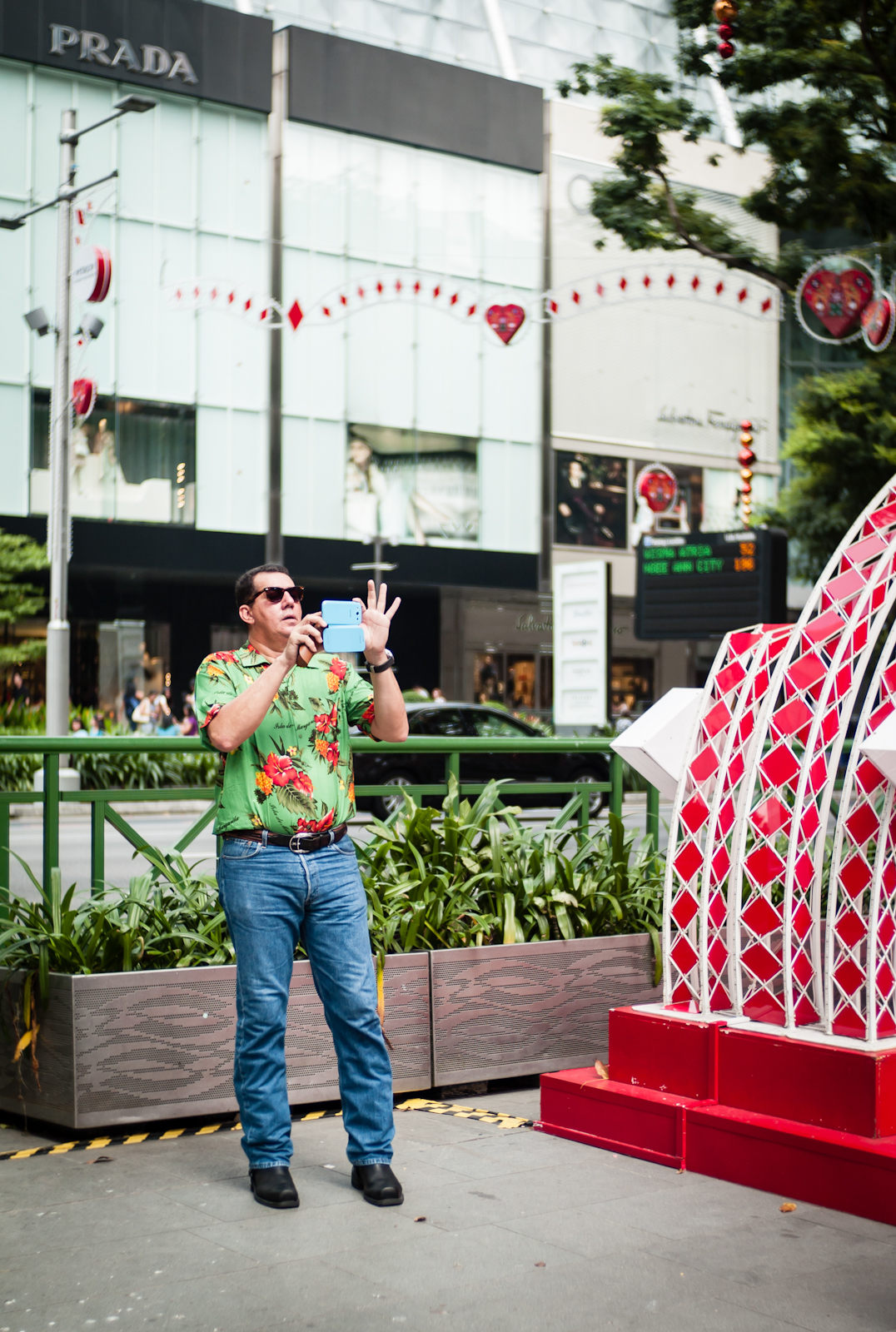 A man in bright clothing taking photos with his smartphone camera