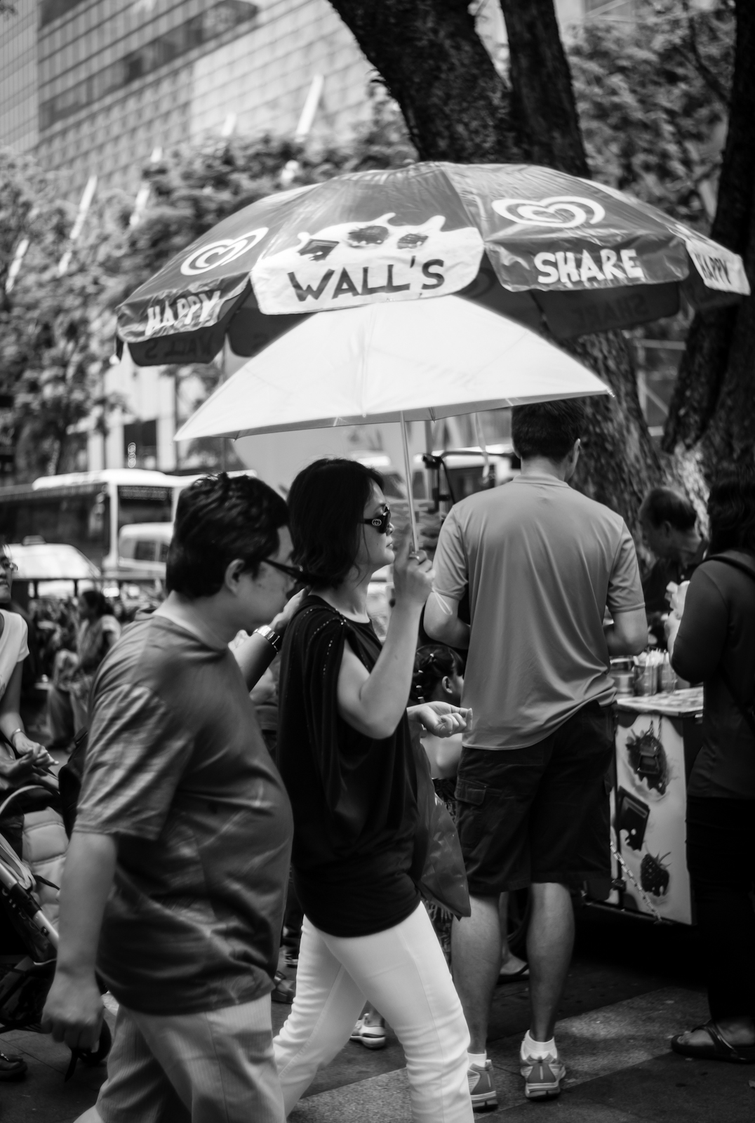 Two woman walking in Orchard Road under an umbrella